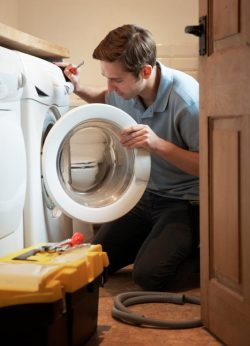 Coach Z's Appliance Repair LLC -Technician Repairing a Broken Washer