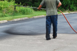 JC Rockland Paving - Man Seal Coating a Parking Lot