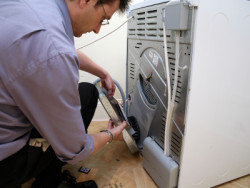 Dependable Appliance Service - Appliance Repair Technician fixing dryer