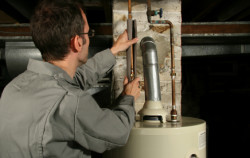 Jim's Service Inc - master plumber working on water heater