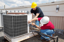 Affordable Heating and Air Conditioning - Professionals installing/repairing an air conditioning unit