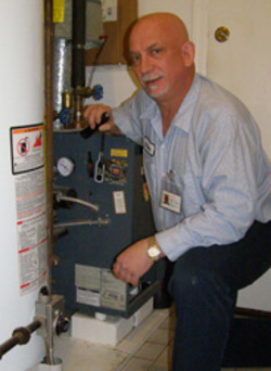 Advanced Rooter Plumbing -Owner Standing next to furnace and water heater