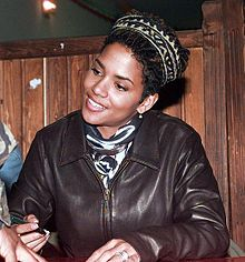 Dressed in brown leather jacket, Berry looks up smiling.