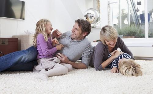 семья лежит играет и балуется на ковре