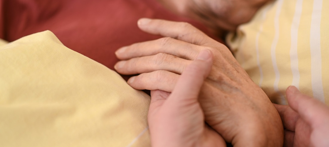 A hospice worker holds the hand of a terminally ill person