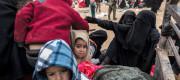 Children and women in burqas climb into trucks in Syria