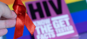 A red HIV ribbon is held in front of a base which is rainbow-coloured
