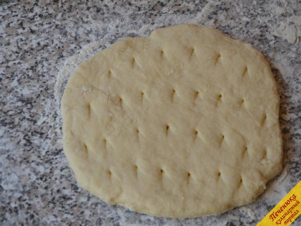 4) Разделить тесто на две или три части, в зависимости от размеров сковороды, и из каждого кусочка раскатать круглую лепешку. Сделать на каждой лепешке дырочки с помощью ножа.