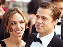 A Caucasian man and woman in the foreground of the image, while others are visible behind them. The woman has brown hair, which is tied back. The man has his dark brown hair parted. He is wearing a black suit and bow-tie with a white shirt.