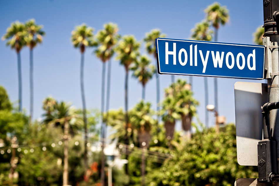 Hollywood street sign with palm trees and blue sky