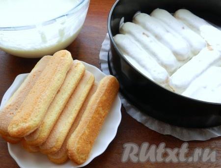 Разъемную форму для выпечки застелить бумагой. Печенье савоярди по одному макать в сметанный крем со всех сторон и выкладывать в форму.