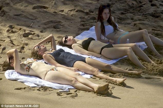 Купание красавицы: девушки растянулась на песке, чтобы пополнить свой загар