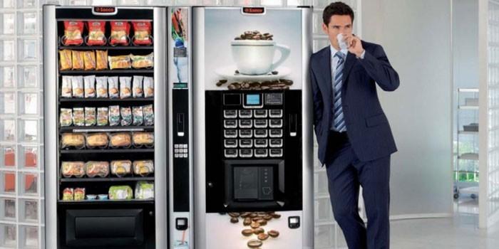 Мужчина пьет кофе у аппаратов