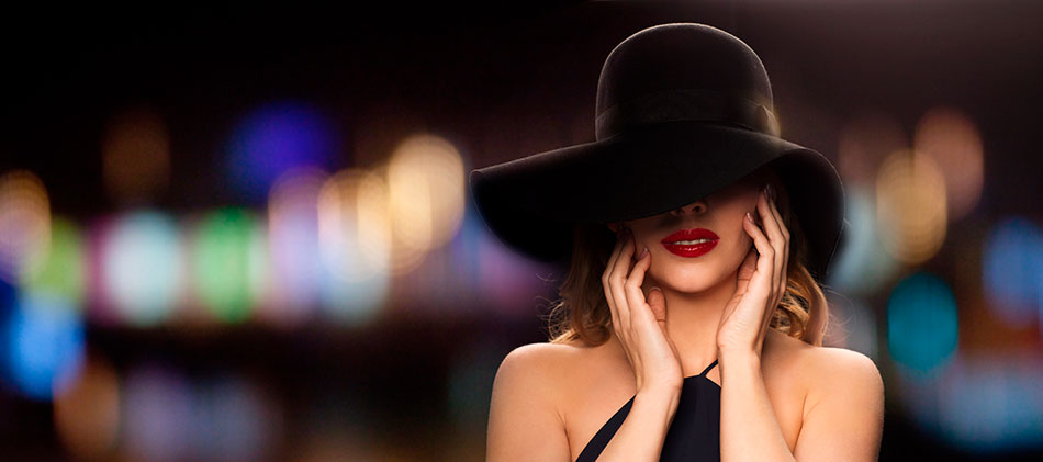 woman celebrity hiding her face with large black hat