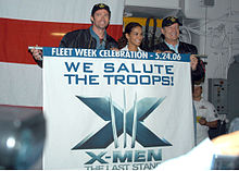 """Hugh Jackman, Halle Berry and Kelsey Grammer hold a flag with the X-Men: The Last Stand logo and the inscription """"We Salute Our Troops"""" in a ship's deck."""