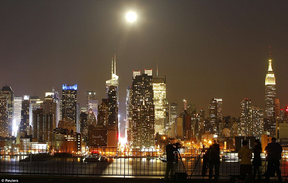 A supernatural delight: The moon appears to be as bright as some of the tallest buildings and busiest parts of New York City. The brightness of Times Square can be seen directly below the moon's rays