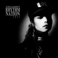 """A young woman photographed in black and white wears an all-black, military-styled uniform accented by silver-plated accessories. A spotlight shines on her face. To her left reads the text """"Janet Jackson's Rhythm Nation 1814""""."""