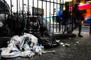 broken,open trash bags in alley