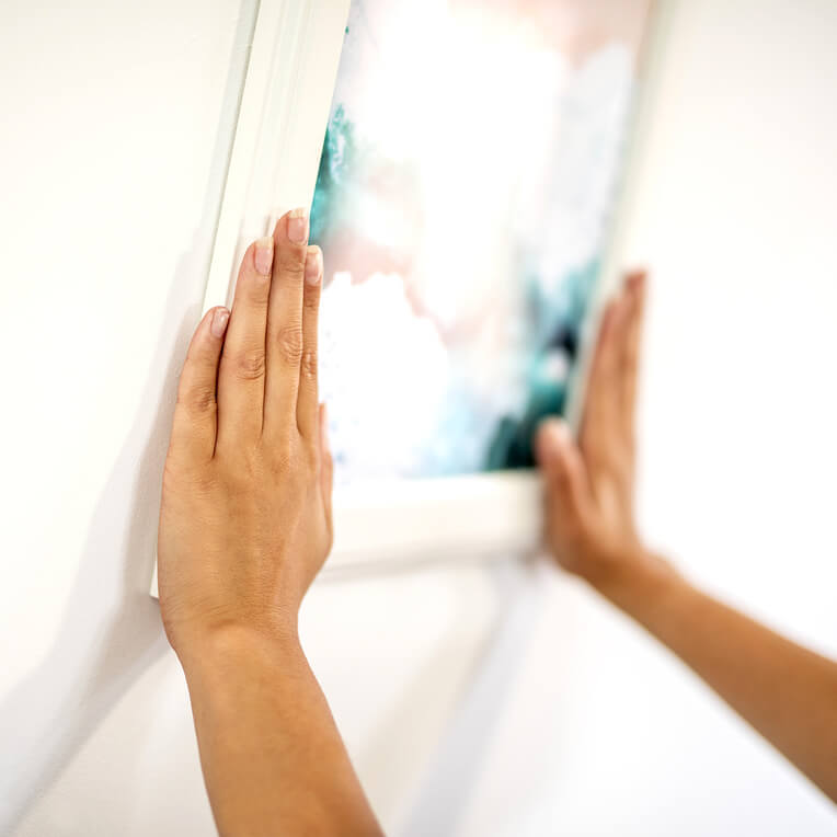 Press down firmly on it for 30 seconds to make sure the picture hanging strips are stuck down securely.