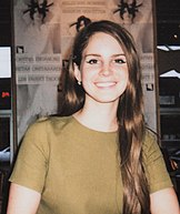 Lana Del Rey, with light-brown hair in an olive-colored shirt, smiling towards the camera at a fan meet