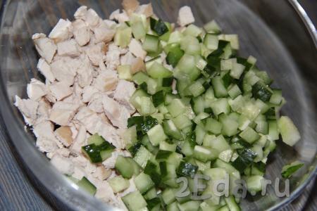 Свежие огурчики вымыть, нарезать на кубики и выложить к нарезанным куриным грудкам.