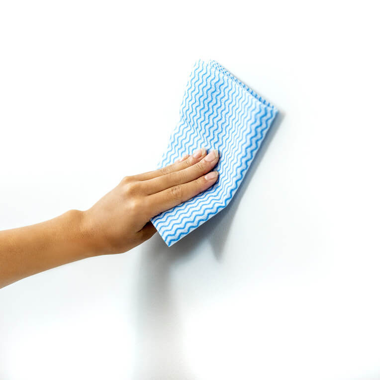 Start by wiping your wall with a damp cloth to remove any dust or dirt.