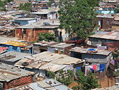 A shanty town located in Soweto, Johannesburg. Many dwellings are shown throughout the photograph.