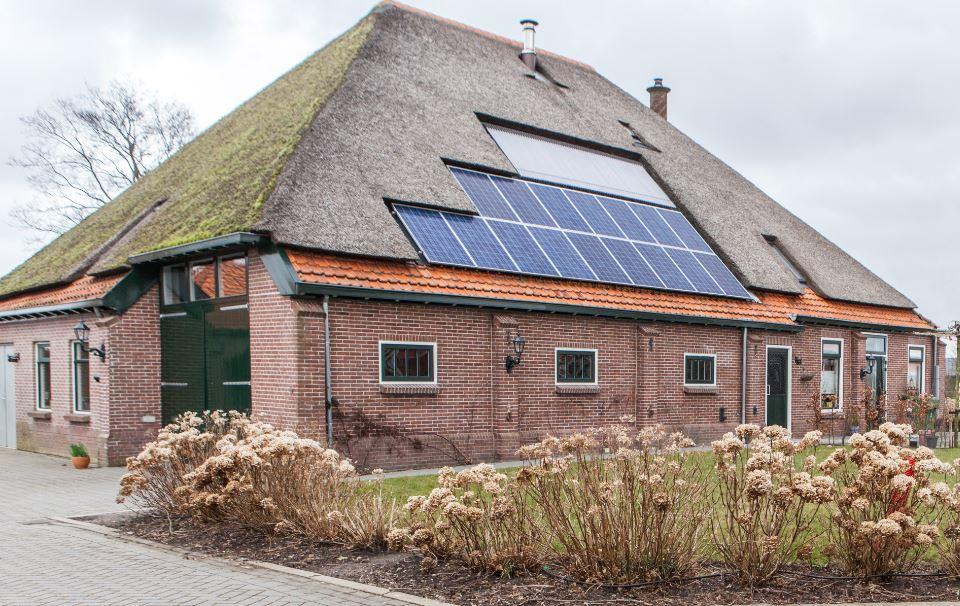 Afbeelding van een stolpboerderij met zonnepanelen op het dak