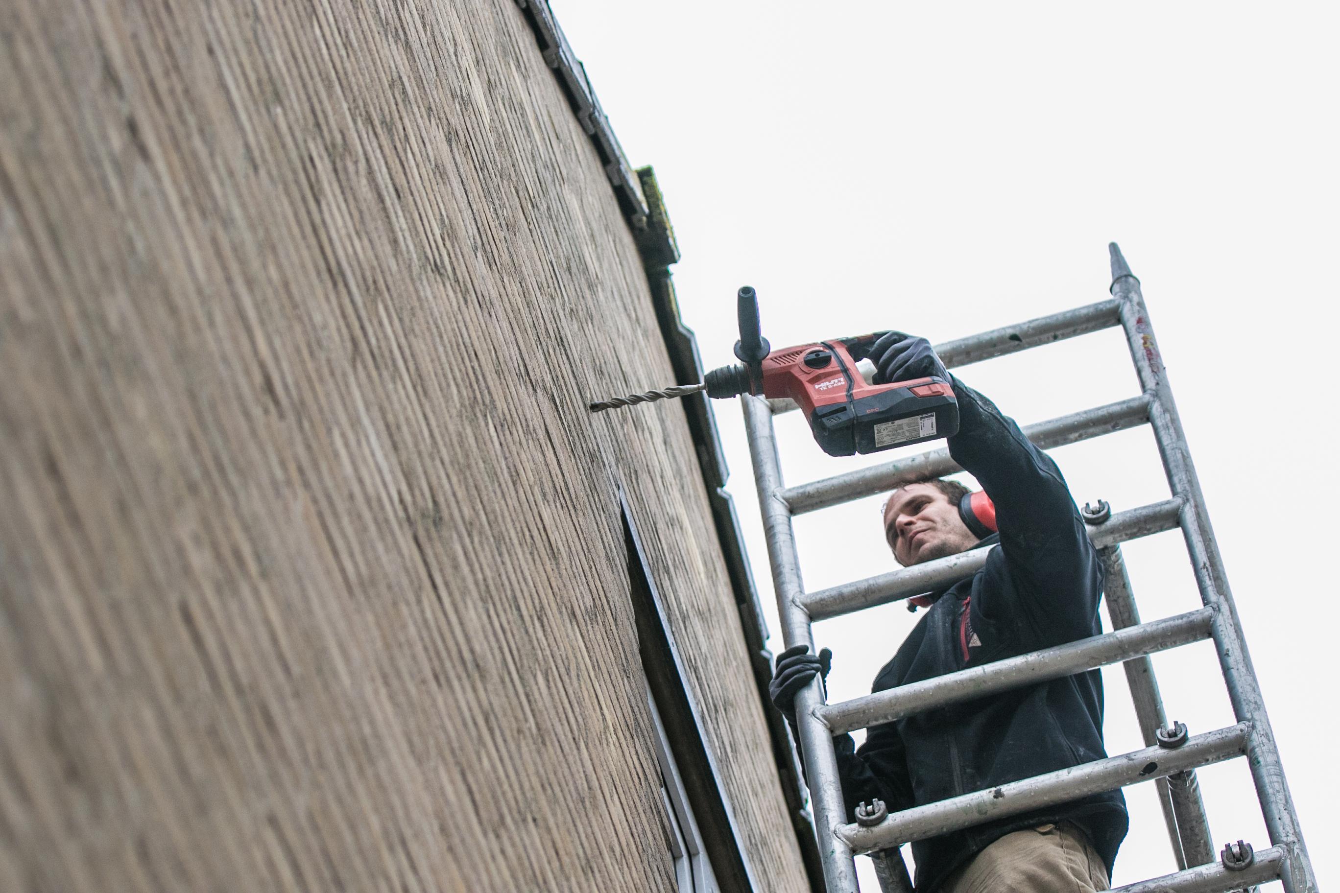 Werknemer isolatiebedrijf boort een gat in de muur van de woning om de spouw te gaan vullen