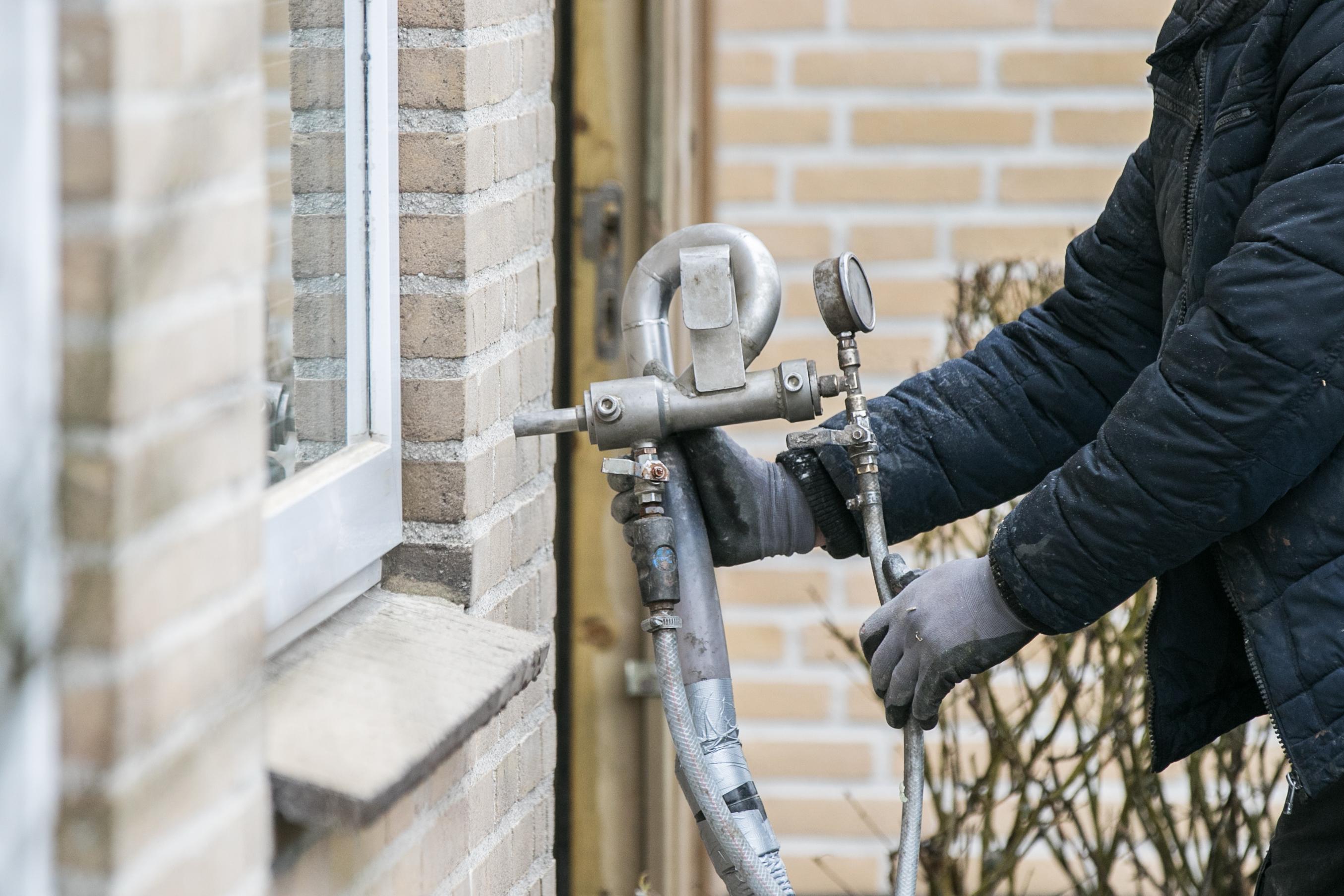 Werknemer isolatiebedrijf spuit isolatiemateriaal in de spouwmuur van de woning