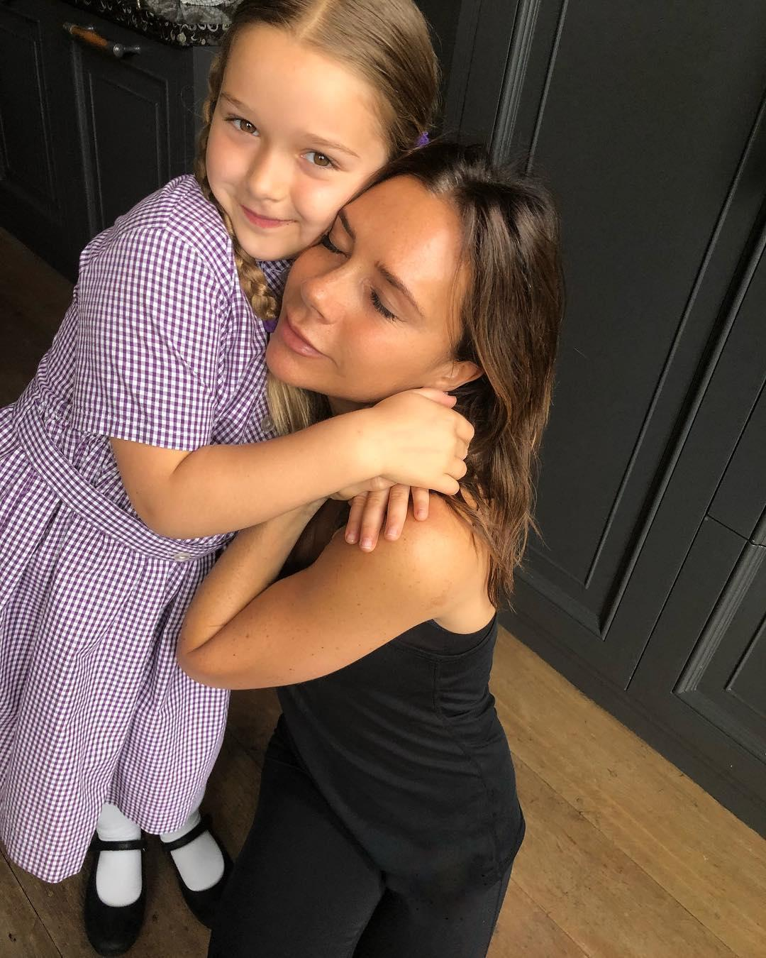 Mum's the word ... Victoria enjoys a hug from daughter Harper, writing on Friday that they 'loved and missed' husband David