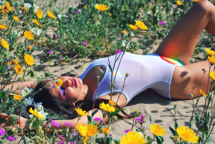 Happy Daze Rainbow Bodysuit in Classic White Mesh & White Daisy Pasties. Laying down in Borrego Springs California Superbloom festival, edc, burning man inspiration.