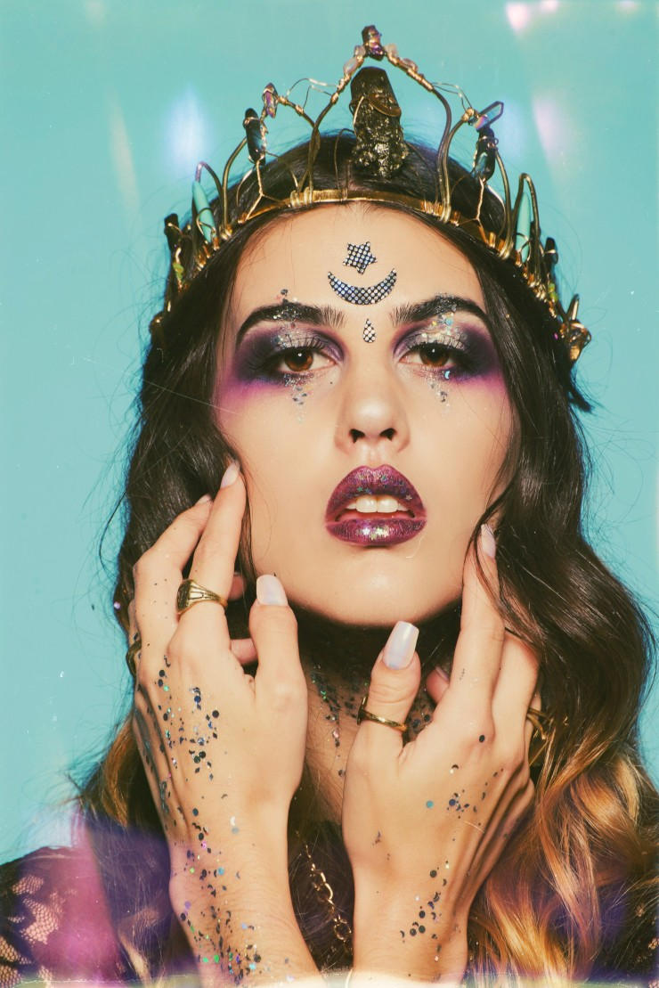 Close up of the beautiful witch wearing stars, moons and glitter on her face.