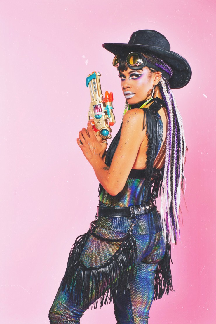 A beautiful black space cowgirl dressed in black fringe holds her galaxy gun.