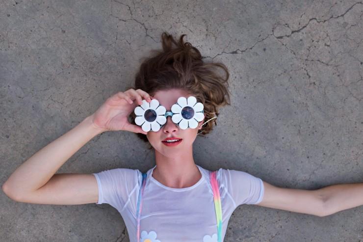 A girl wearing daisy Marina Fini sunglasses lays on the ground.