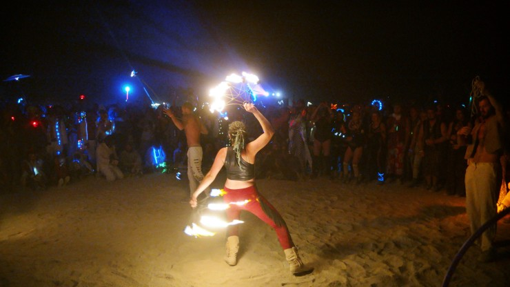 A girl performing with fire fans at Burning Man.