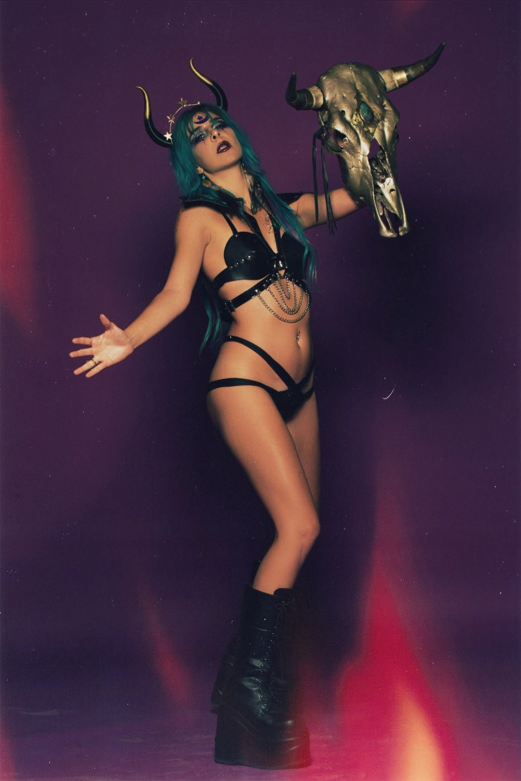Blue haired bull horned zodiac warrior goddess wearing harnesses and vegan leather.