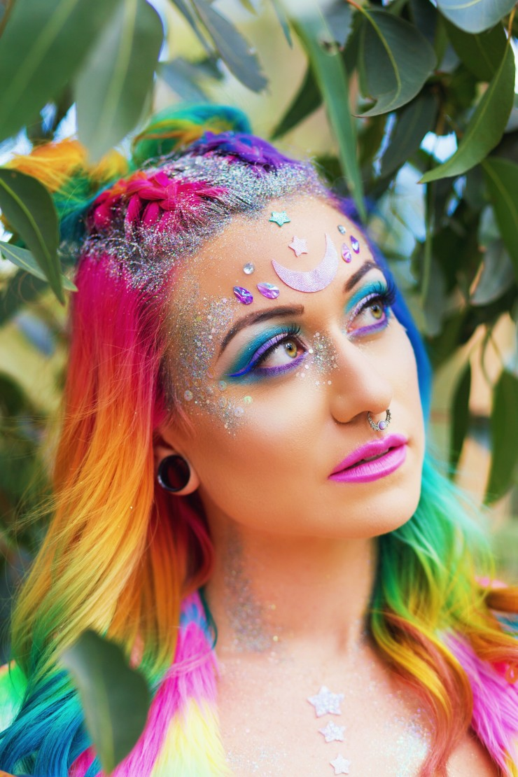 Rainbow haired girl wearing an all rainbow tie dye look and glittery makeup.