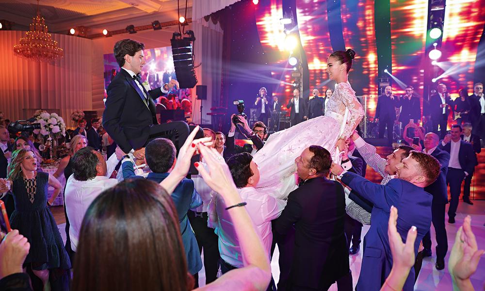 Во время исполнения еврейского танца хоры молодоженов потрадиции подняли настульях ичествовали какцаря с царицей