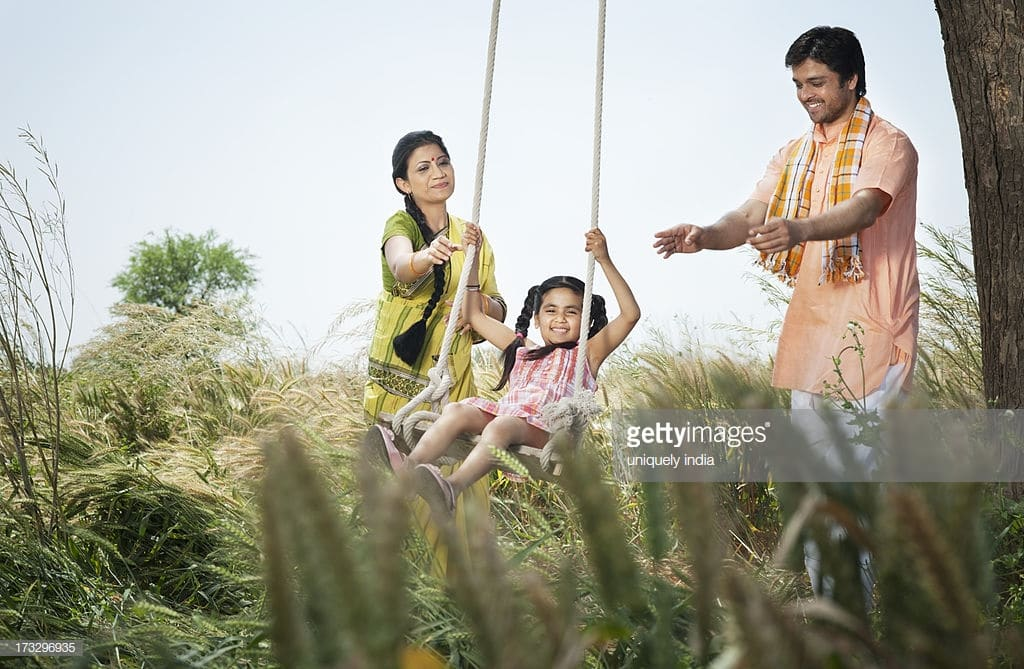 Rural family enjoying with a swing in the field, Sohna, Haryana, India