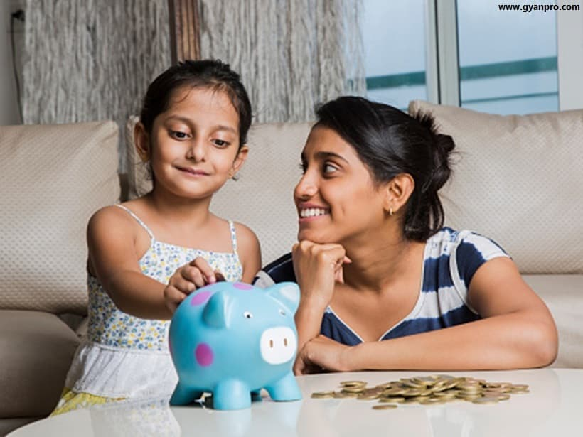Mother and daughter putting coins into piggy bank - Stock image