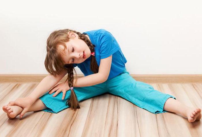 Девочка выполняет упражнение для растяжки