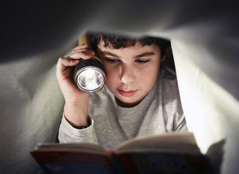 Мальчик читает под фонариком
