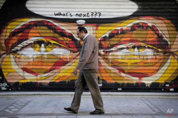 In this photo made on Tuesday, April 29, 2015, a Greek man walks past a graffiti in central Athens. (AP Photo/Petros Giannakouris)