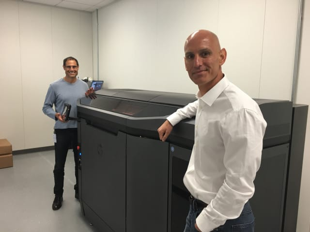 John Dulchinos (left), VP, Global Automation and 3D Printing, and Bill Muir, COO, at Jabil's San Jose additive manufacturing lab, next to one of the first production units in North America of HP's Jet Fusion 3D Printer. (Image courtesy of HP.)