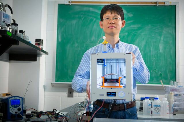 Chi Zhou holding a modified Ultimaker 3D printer used to produce the graphene parts. (Image courtesy of Kansas State University.)