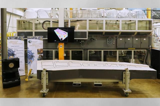 ORNL and Boeing's 3D-printed tooling in front of the BAAM 3D printer. (Image courtesy of ORNL.)