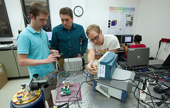 Assistant physics professor Michael Zemcov, center, works with BS/MS electrical engineering majors Kevin Kruse (left) and Benjamin Bonder (right) in the RIT Center for Detectors. (Image courtesy of A. Sue Weisler/Rochester Institute of Technology.)