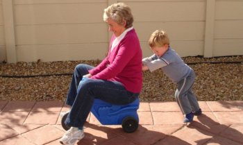 Child_pushing_grandmother_on_plastic_tricycle.jpg