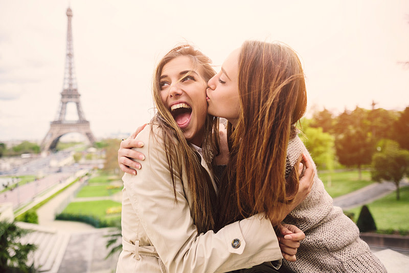 two-girls-embracing-kiss-on-cheek-in-romantic-Paris-eiffel-tower-in-background
